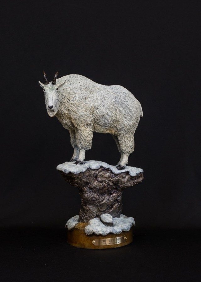 A goat standing on a snow covered rock in the bronze sculpture 'The Wise Man'.