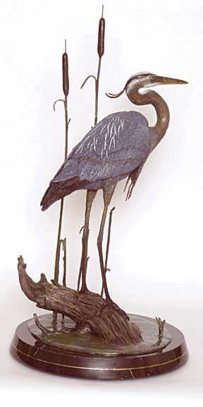 A blue heron stands near cattails in the bronze 'Morning Grace'.