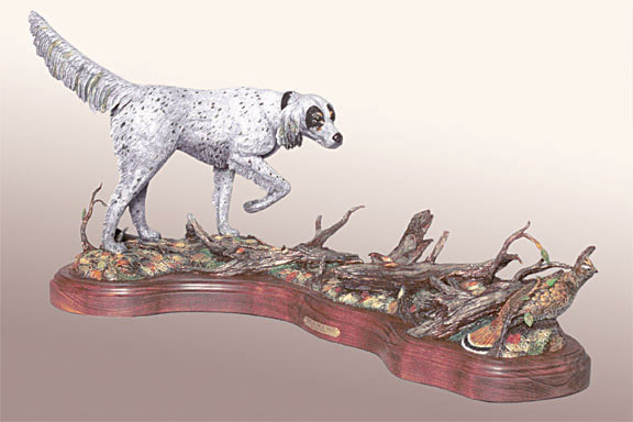 An english setter points to quail among fallen limbs in the bronze 'Point on the Au Sable' by Devin Rowe.
