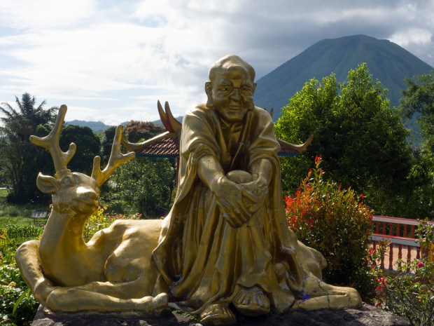 Statue in front of mount Lokon at Buddhist temple with pagoda and statue in Tomohon (Sulawesi, Indonesia)