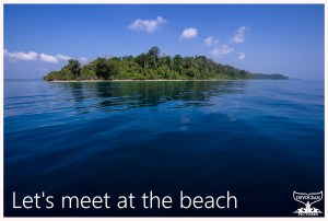 Long Island, Andamans, India, is shimmering as a lush green tropical oasis in the deep blue see against lighter blue sky. Postcard with warm regards: Let's meet at the beach.