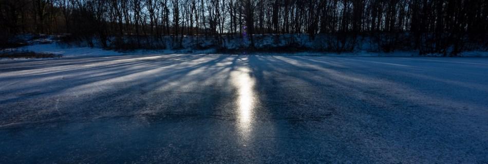 """Titelbild zu """"Richtig Stimmung unter dem Gefrierpunkt"""". Zugefrorener kleiner See in den Niederlanden. Die Sonne scheint durch die Bäume am gegenüberliegenden Ufer, die ihre Schatten auf das dunkle Eis und die dünne Schneeschicht, die den See noch zu Teilen bedeckt, werfen. Wolkenloser, blauer Himmel dazu."""
