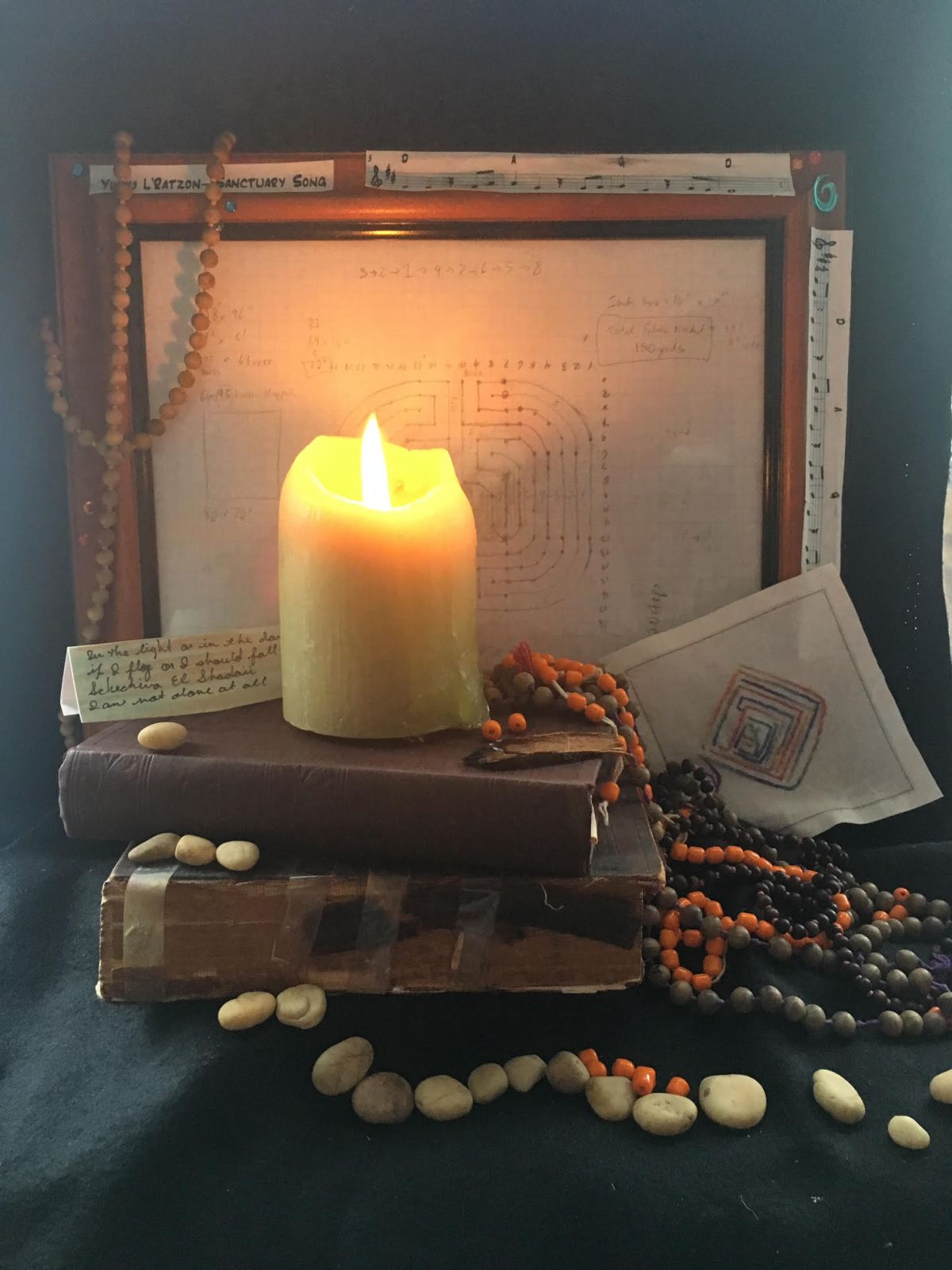 Photo of altar with calendar, hebrew text, mala beads, stones, and hebrew labyrinth