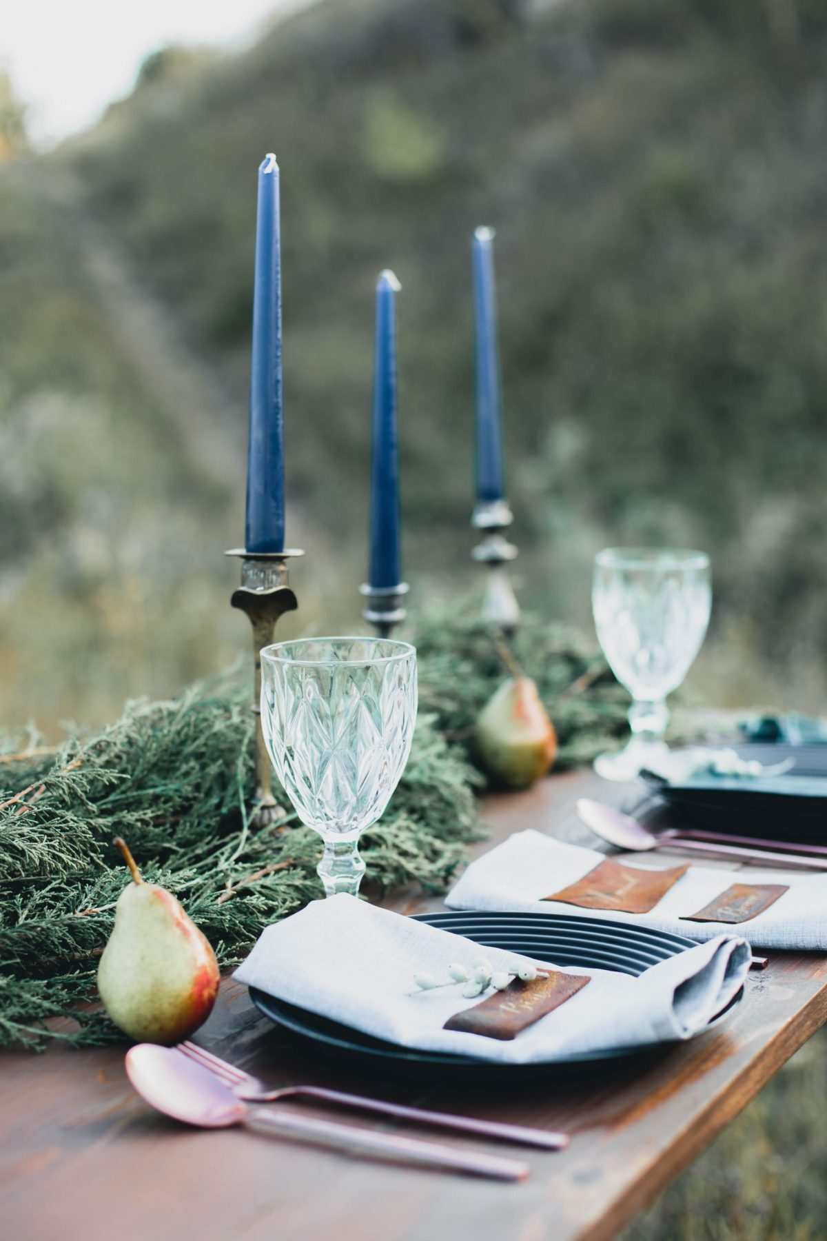 Outdoor place settings, with blue candle sticks, goblets, napkins, greenery and pears