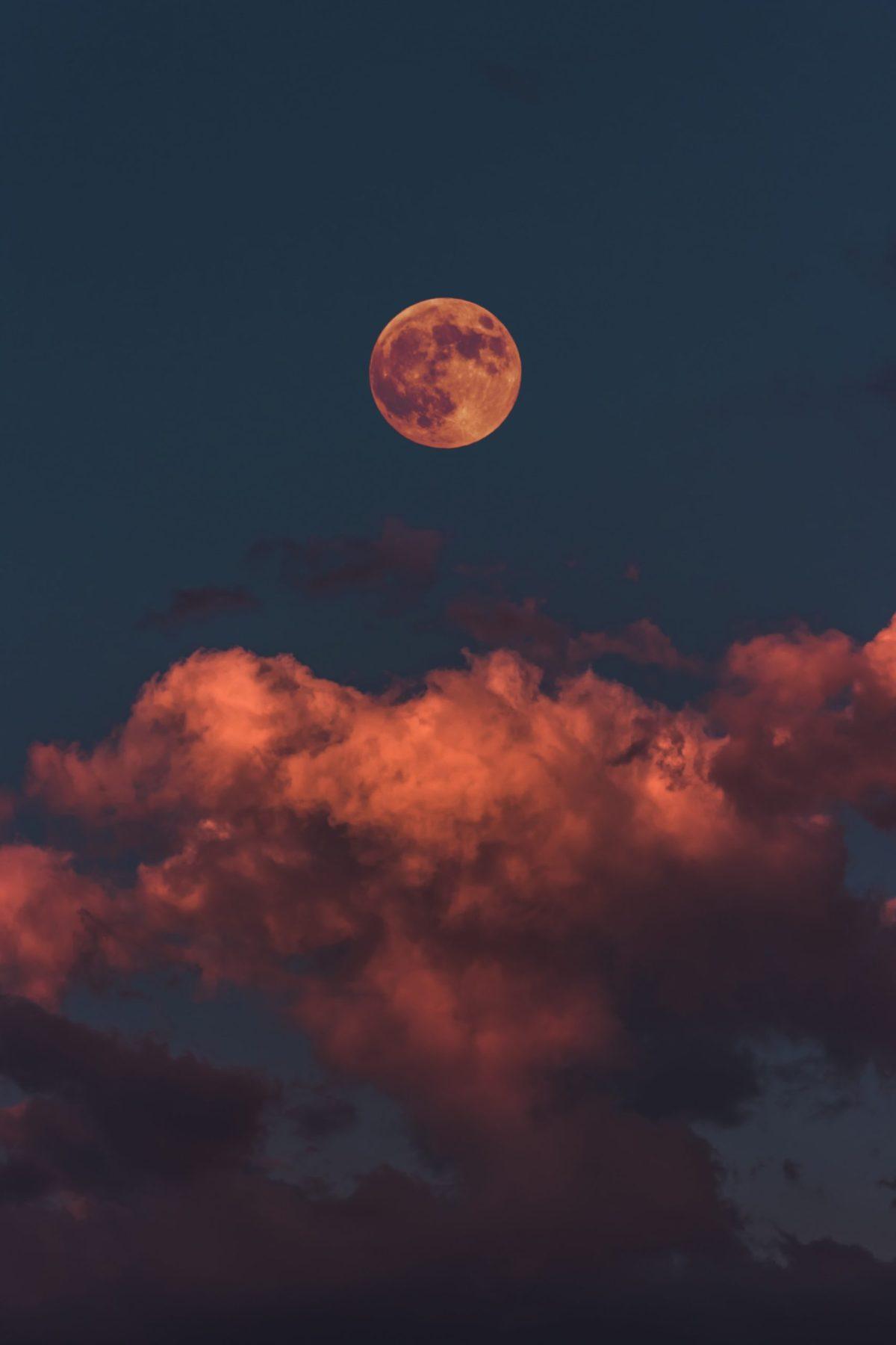 Orange Moon and clouds in a darkening sky
