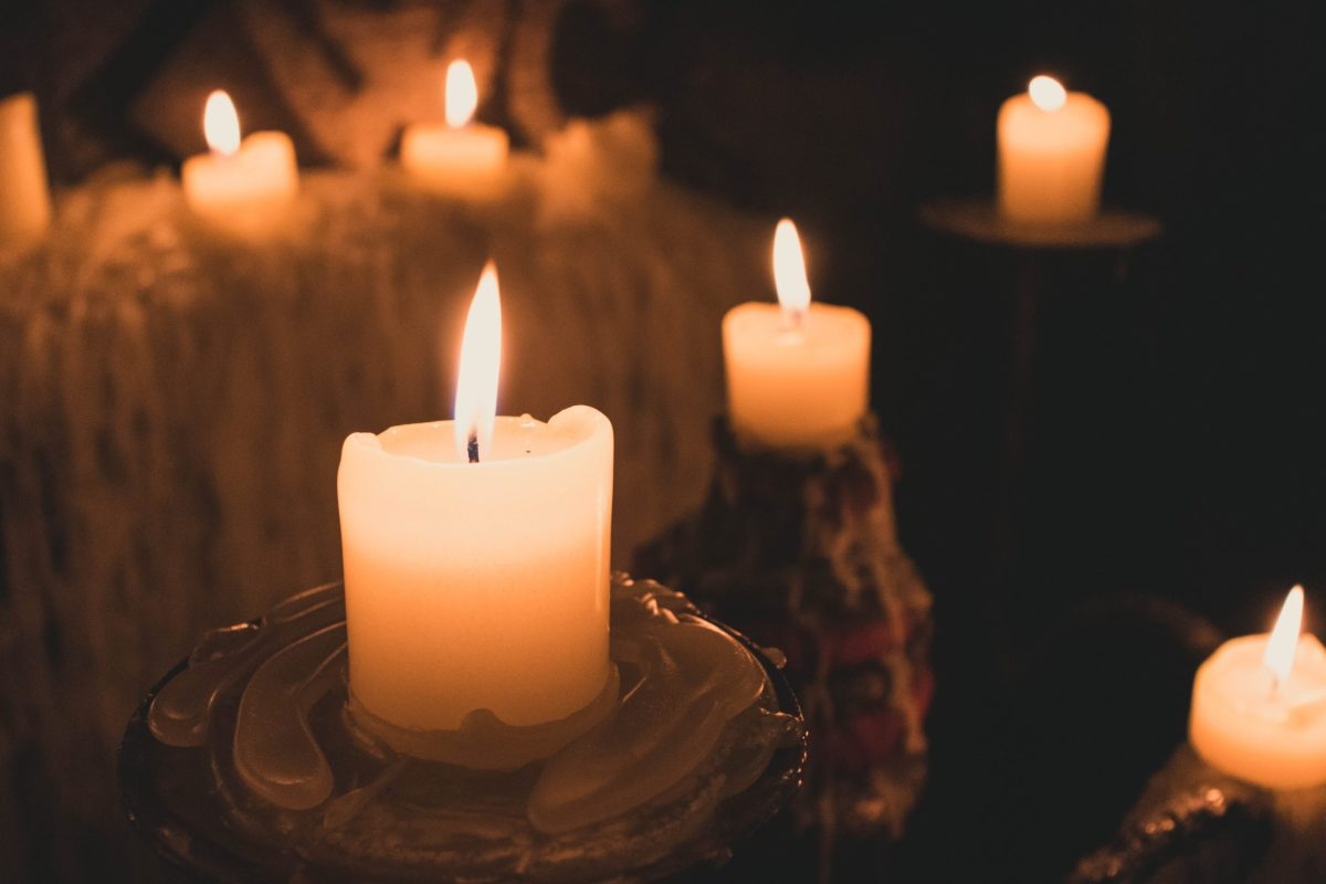 Small white candles light up a dark cavernous space