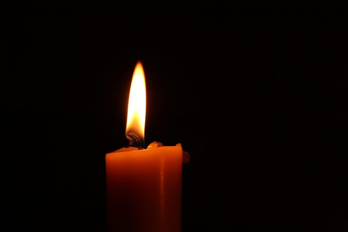 A close up of a single red lit candle