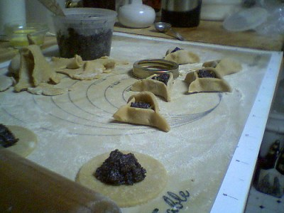 Hamantaschen in various stages of preparation on a baking sheet before going in the oven