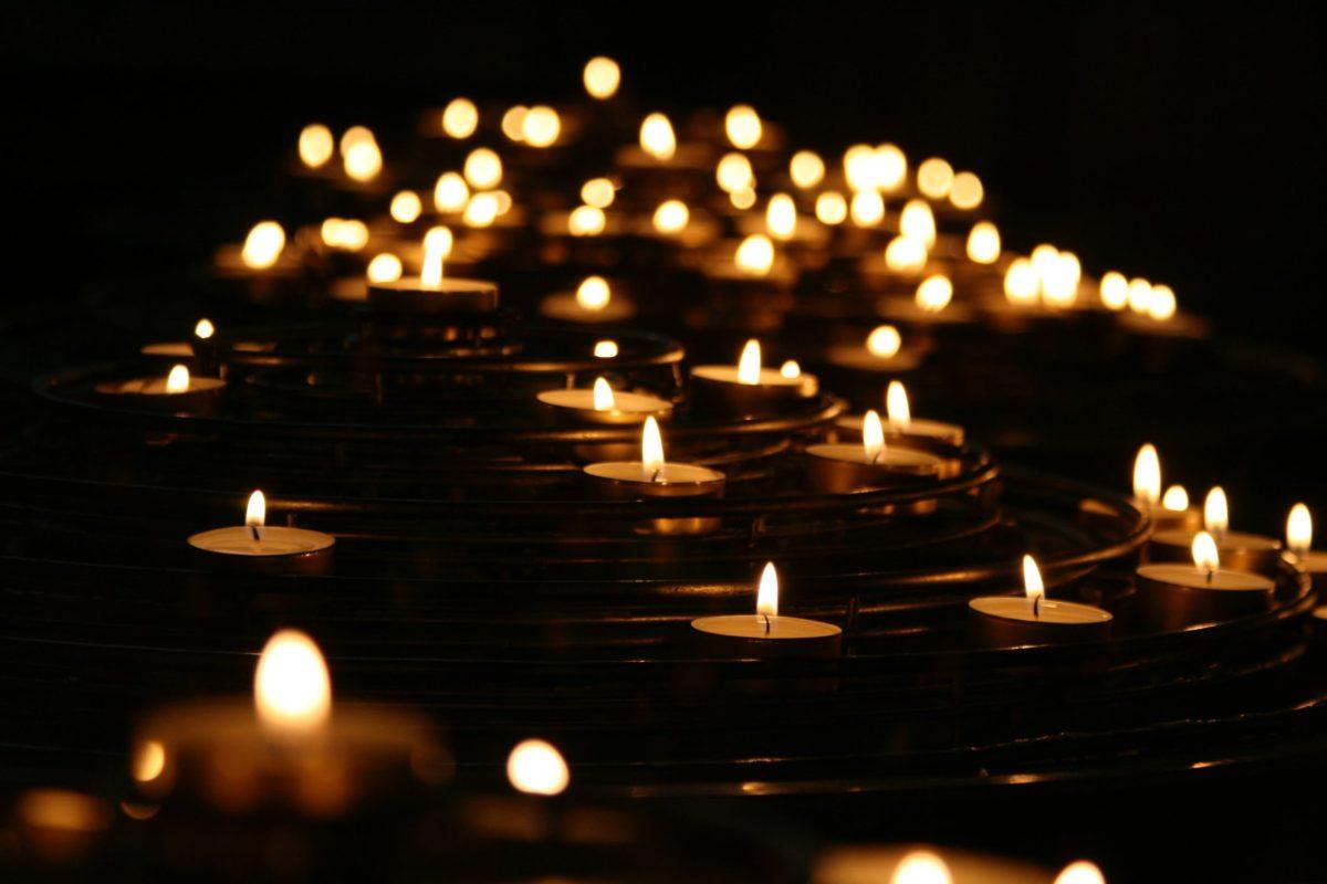Many lit tea lights in spread across a surface in a dark room