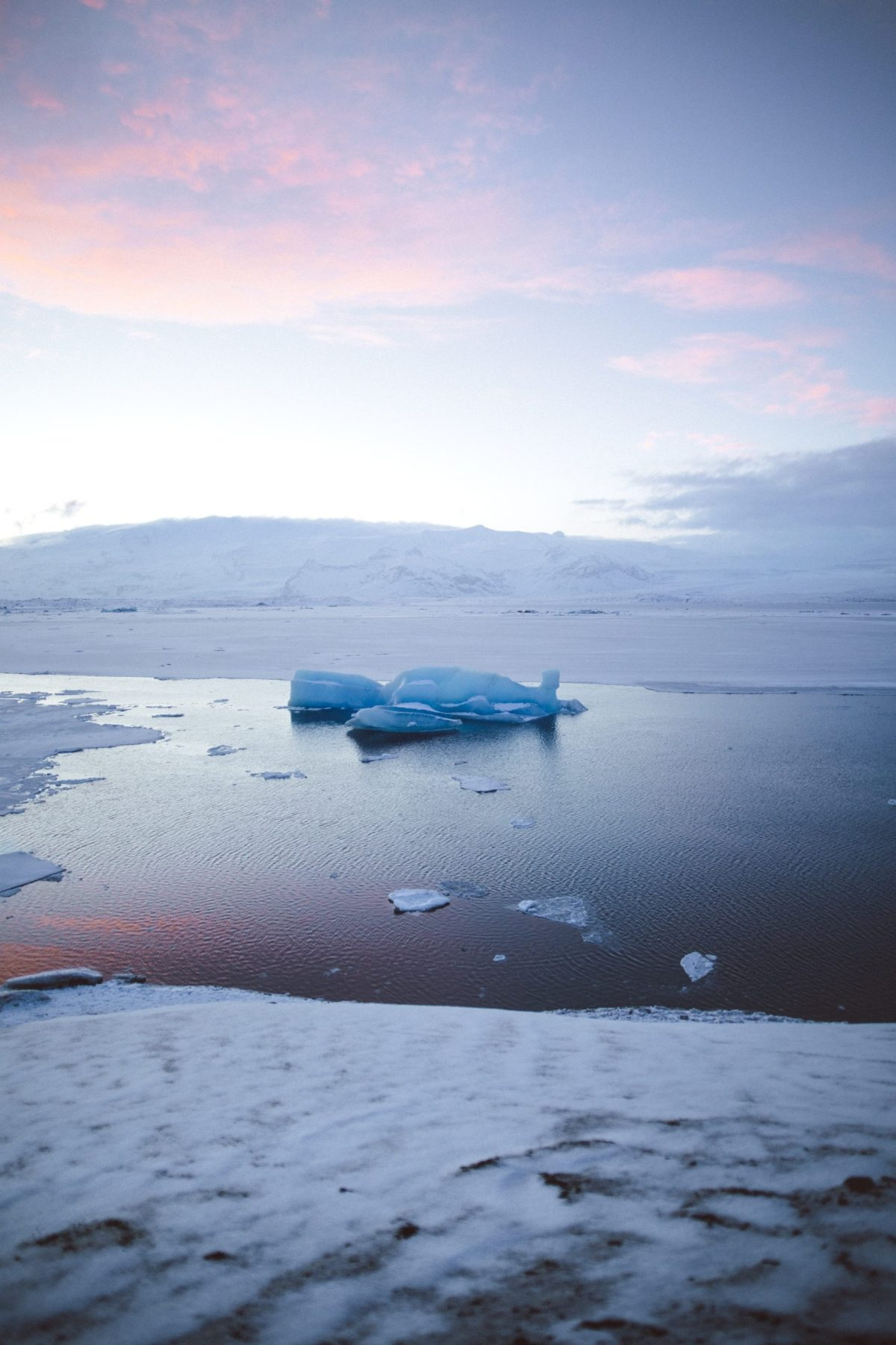 Icy, wintery landscape, it might be just after dawn or just before dusk as there are pink cloud in the distance