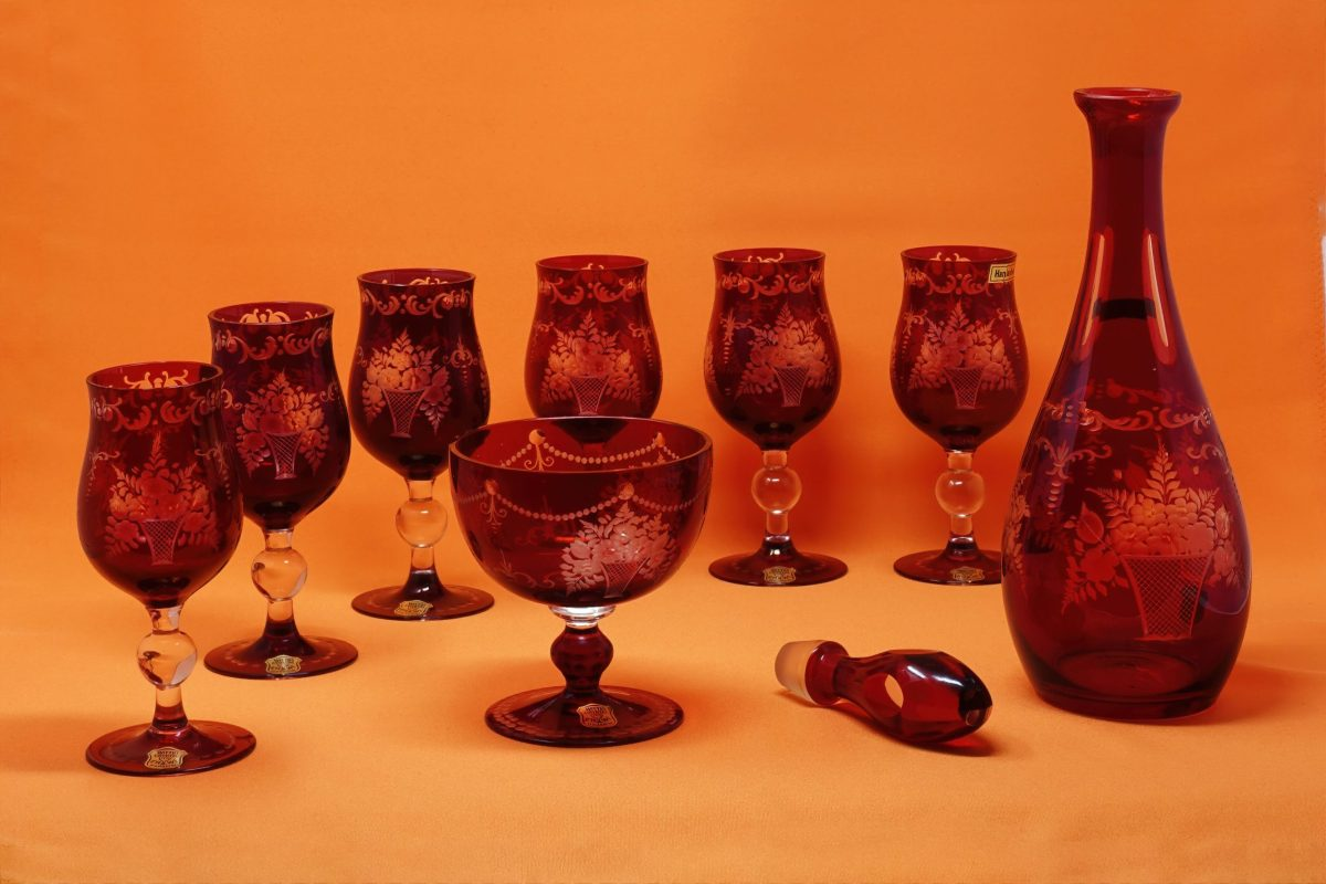 7 ornate red and clear glass goblets and one matching decanter with an orange background