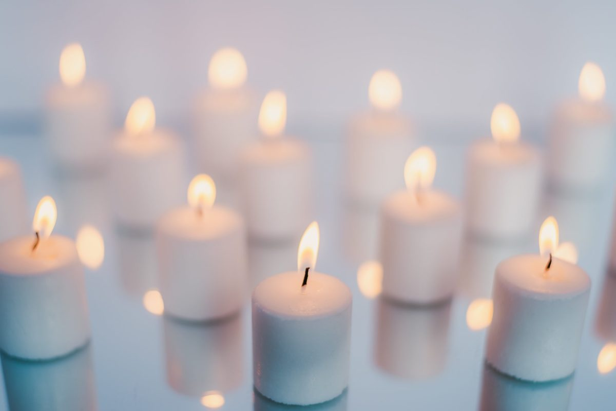 Many just lit, short, white candles