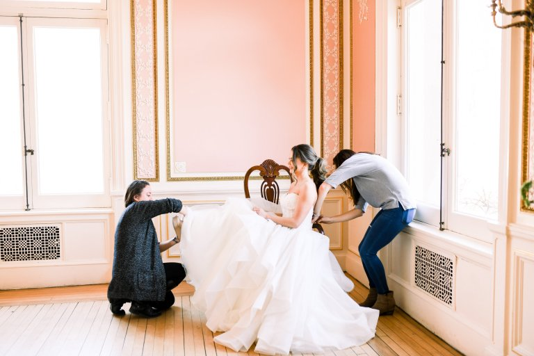 wedding planner fixing wedding shoes on bride