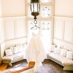 wedding gown hanging from fixture on staircase landing