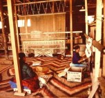 NAVAJO WOMEN WEAVE A RUG AT TRADING POST ON THE NAVAJO RESERVATION wikipedia public domain