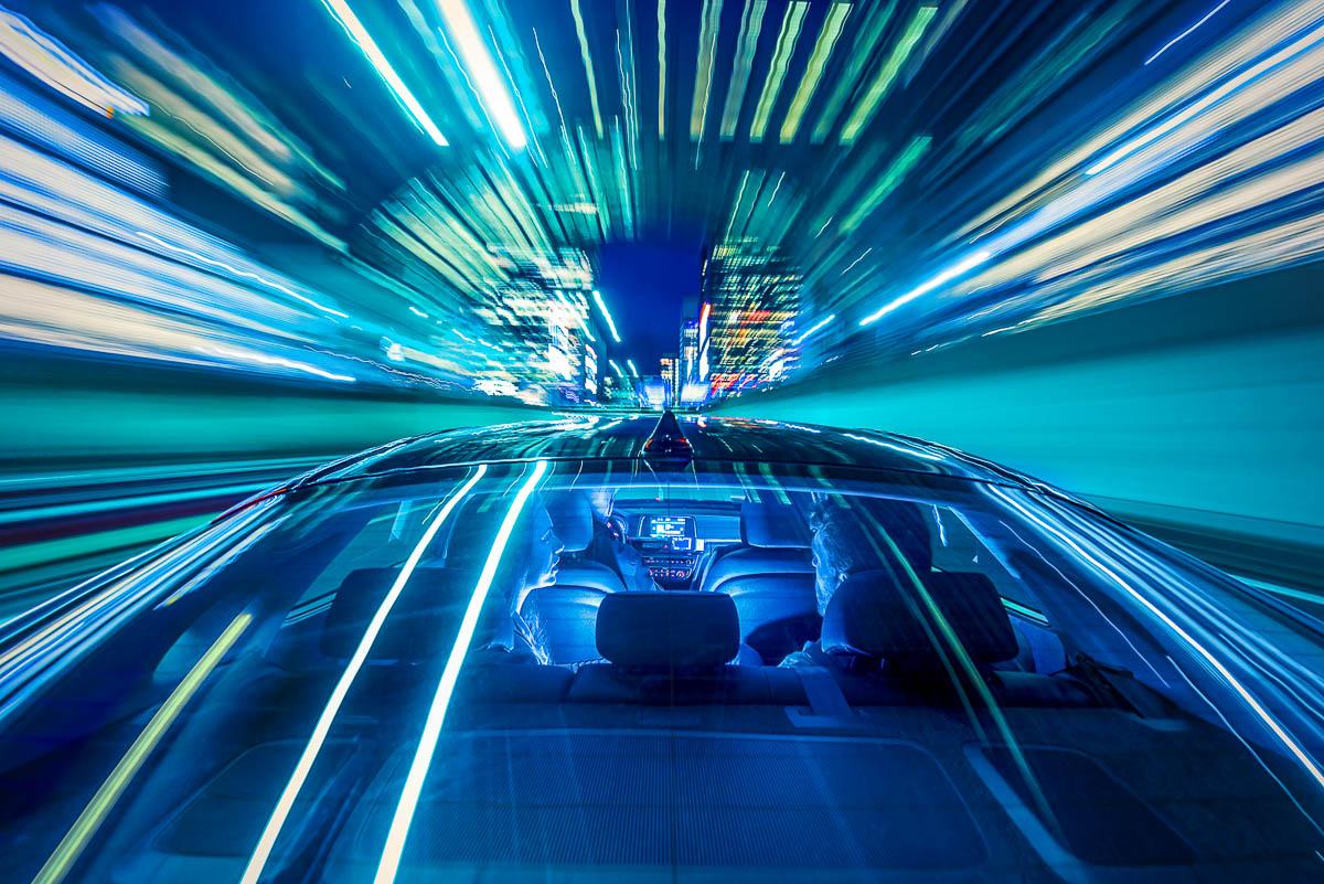Een auto rijdt 's nachts door een verlichtte tunnel, met twee mensen op de achterbank.