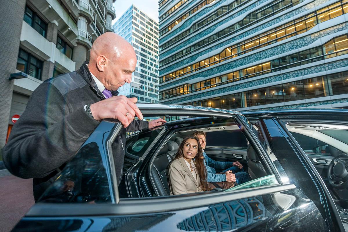Taxichauffeur opent het portier voor zijn klanten in de binnenstad van Den Haag