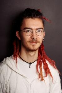 Hij is Jesse; een filosofie-student, muzikant en theaterenthousiasteling met slechte smaak. Voor Lijkzang is hij regisseur, Hoofd Acteurs en Hoofd Muziek. Ik ben een hydra, want: veel hoofden.