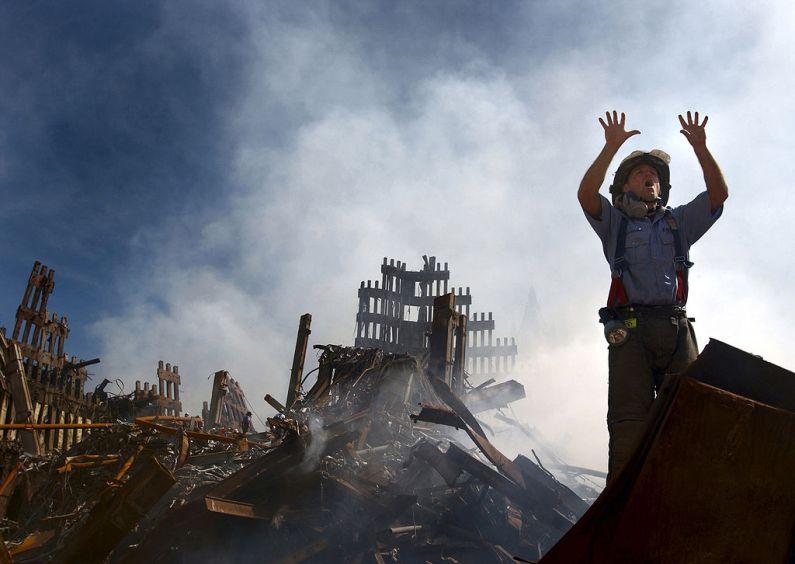 Un pompier din New York City cheamă încă 10 lucrători ai serviciilor de urgență să intre între dărâmăturile de la World Trade Center. Foto de Preston Keres, sursa Wikipedia.