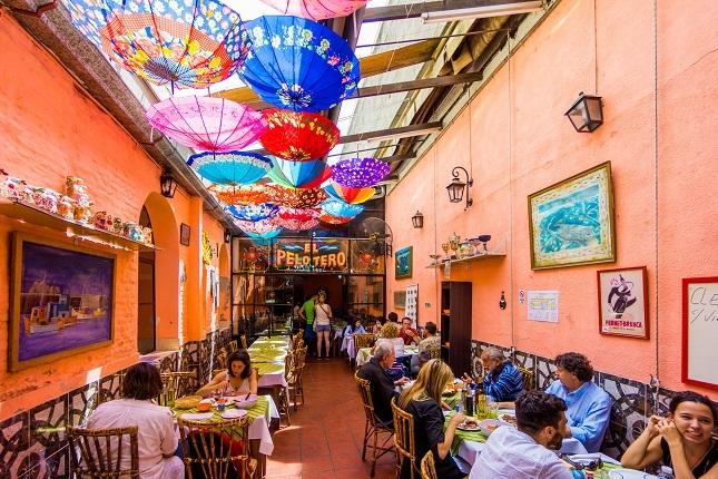 Ein argentinisches Restaurants mit bunten Schirmen an der Decke. Hier kannst du leben wie die Einheimischen auf deiner Südamerika Reise.