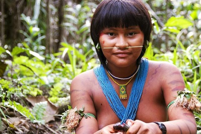 Indigene Völker im Amazonasgebiet: Eine junge Frau des Yanomami Stammes mit blauen und grünen Halsketten und einem gelben Stäbchen als Nasenschmuck schaut in die Kamera.