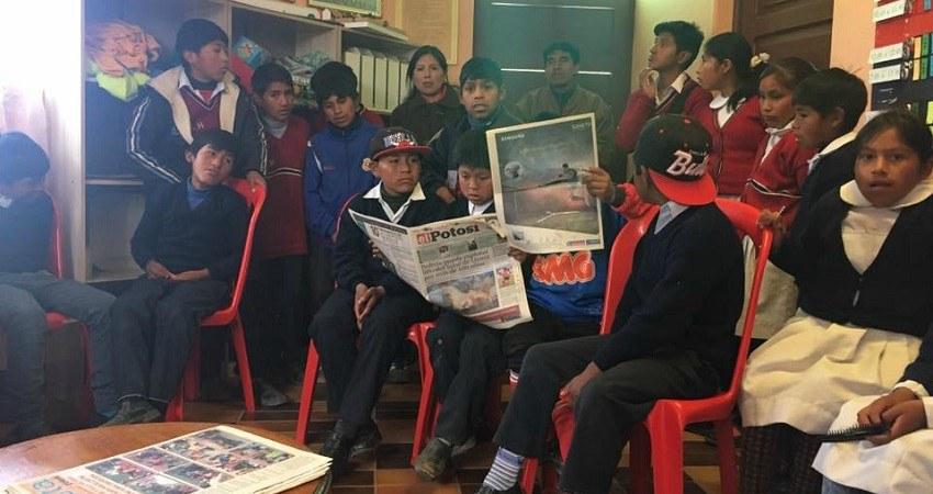 Kinderrechte in Bolivien: Treffen mit jungen Gewerkschaftlern in Potosí. Eine Gruppe Kinder sitzt auf Plastikstühlen und liest die Tageszeitung von Potosí.