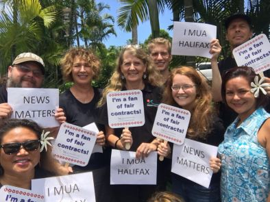 "In Hawaii, Guild members show support for the News Matters campaign and striking members in Halifax, Nova Scotia. ""I mua"" (pronounced ee mua) means ""forward"" in Hawaiian. Kamehameha the Great used it as part of his famous battle cry: ""I mua e na pokii a inu I ka wai awaawa aohe hope e hoi mai ai."" ""Forward my young brothers and drink of the bitter waters of battle, for there is no turning back until we are victorious."""