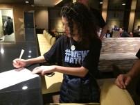 Elizabeth Hernandez of The Denver Post signs the group letter to Alden.   Julie Reynolds