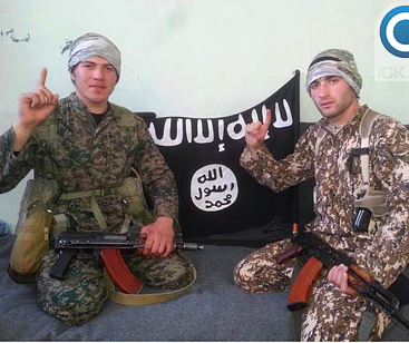 Two teenage boys seated, dressed in military fatigues with machine guns, IS flag in background