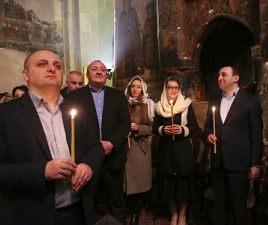 Government members holding candle lights inside a church