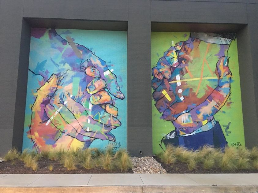 Two large Adrian Torres murals of hands clasping
