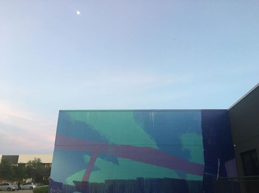Adrian Torres mural depicting twilight before a half moon at sunset