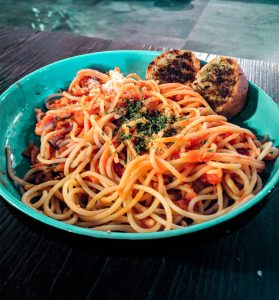 blue bowl filled with spaghetti and garlic bread
