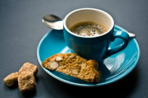 half-full cup of coffee with biscotti on turquoise plate