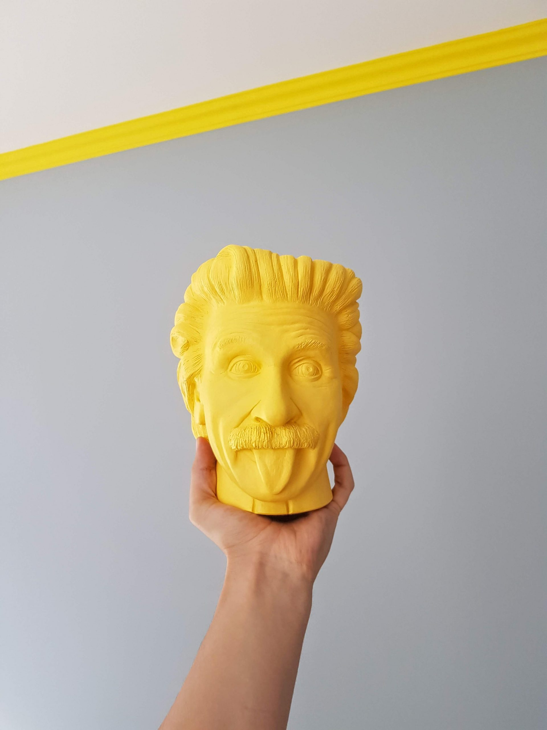 """a hand holding a """"toy"""" yellow head of Einstein sticking his tongue out"""