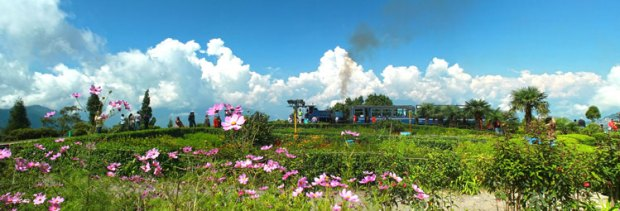 Batasia Loop Darjeeling. Batasia means airy space. the As you stand on one side of the garden and see the toy train making a complete loop while hooting its whistle along the way and trying to negotiate the spiral track with a double loop, it's a fabulous experience.