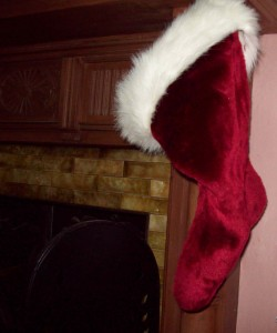 Red stocking with white fur trim hung on a fireplace.