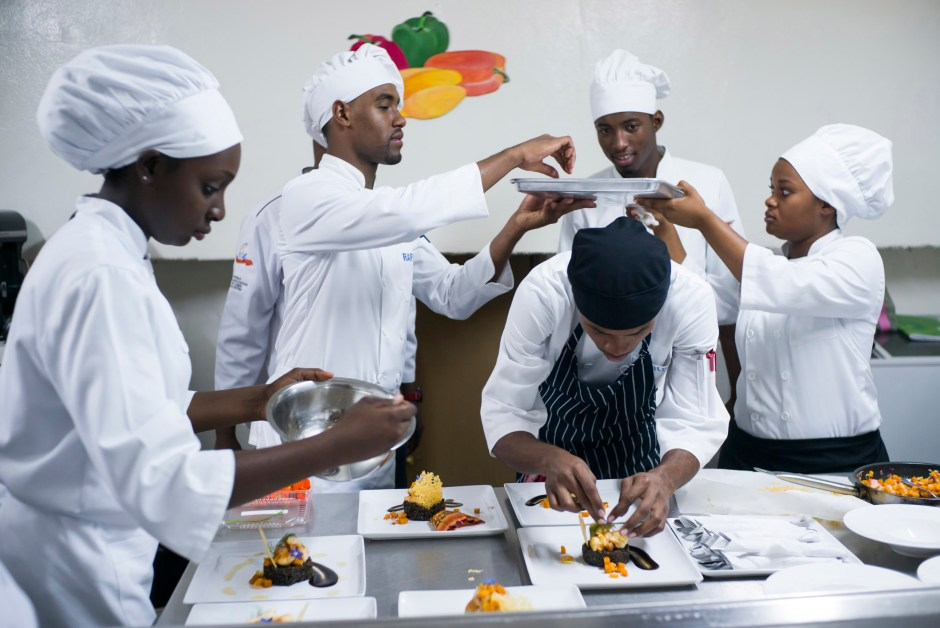 © Corentin Fohlen/ Divergence. Port-au-Prince, Haiti. 27 octobre 2015. Formation professionnelle dans l'hotellerie a l'ecole hoteliere d'etat. Cette ecole est soutenue par le ministere du tourisme. 290 eleves sont formes chaque annee. La formation comprend des cours de cuisine et patisserie, de gestion d'un bar et d'un restaurant, et de receptionniste. Haiti manque de professionnels et les hotels nouvellement crees comme le Marriott, le Best Western ou le Royal Oasis ont besoin d'un main d'oeuvre qualifiee. De plus en plus de jeunes haitiens cherchent a travailler dans le domaine du tourisme, mais les debouches manquent. # Une partie de la formation est soutenue par l'ONG americaine de chefs cuisiniers, World Central Kitchen (WCK), cree par le chef Jose Andres.