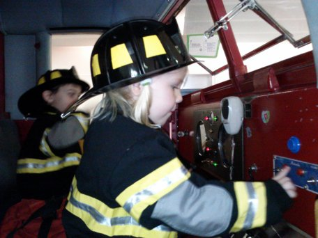 Fiona sits in the cab of a firetruck at the Staten Island Children's Museum.