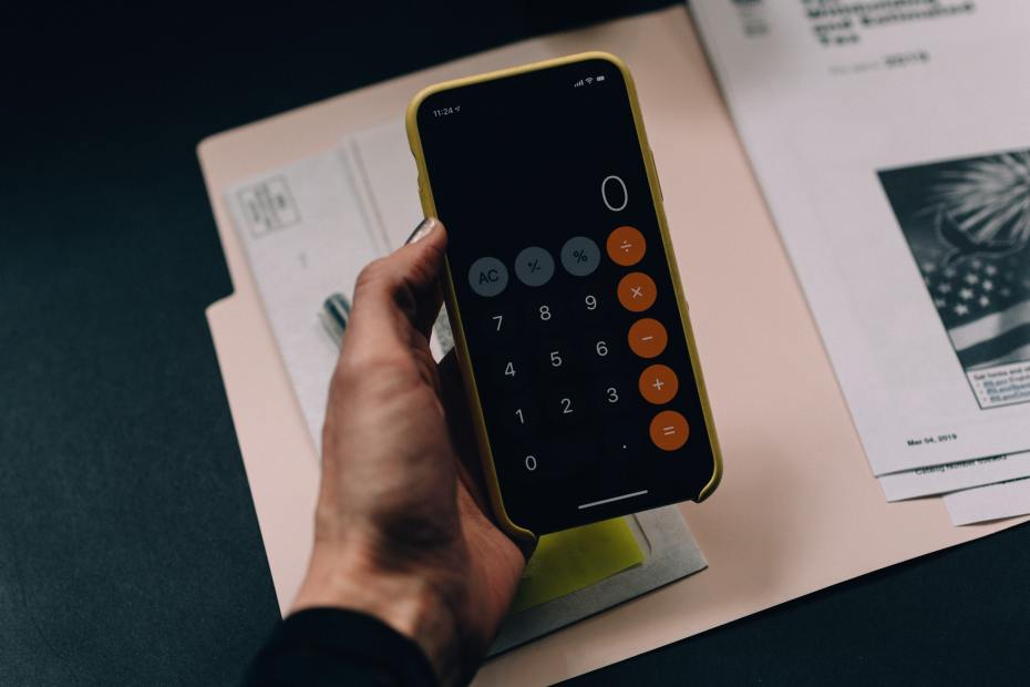 A hand holds a phone with calculator on over a file of documents