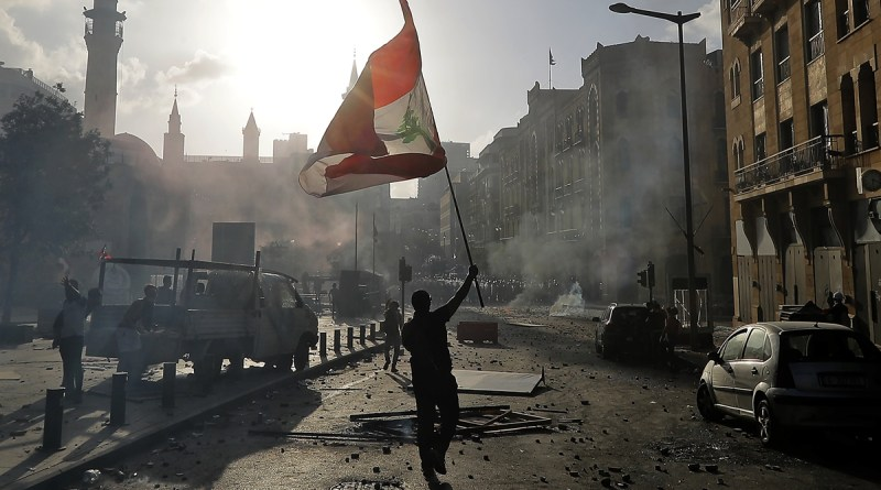 A Lebanese protester waves the national flag during clashes with security forces in downtown Beirut. Photo: AFP, Globaltimes
