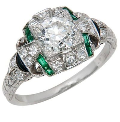An Art Deco platinum, diamond, emerald and onyx engagement ring. Via Diamonds in the Library.
