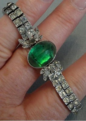 Art Deco bracelet with double strand rhinestones and a green cabochon clasp, marked sterling, circa 1919.