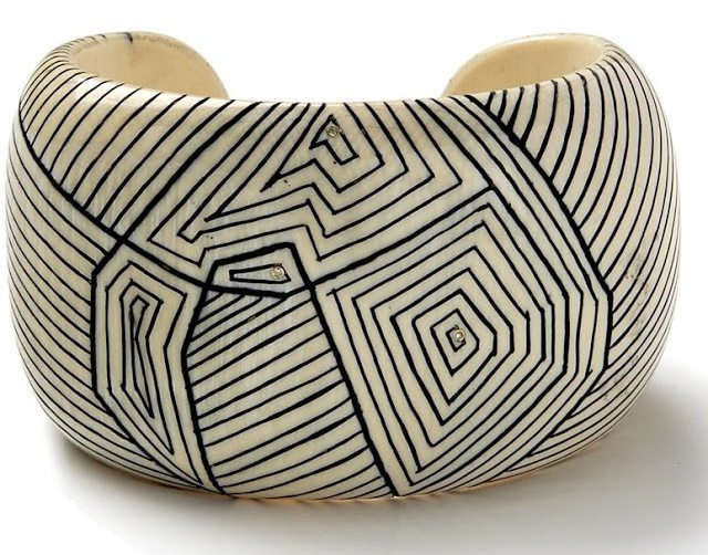 Fossilized woolly mammoth cuff with hand carved scrimshaw and white diamond inlay. By Monique Pean. Via Diamonds in the Library.