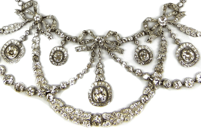 Close up view of a Belle Epoque diamond garland necklace with tiny bows, circa 1900. Via Diamonds in the Library.