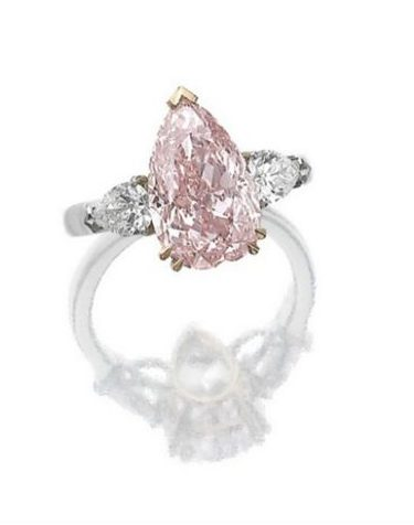 Diamond ring with a 4.59 carat fancy intense pink pear-shaped diamond. The pink center stone is flanked by two pear-shaped diamonds, mounted in platinum and pink gold. Via Diamonds in the Library.