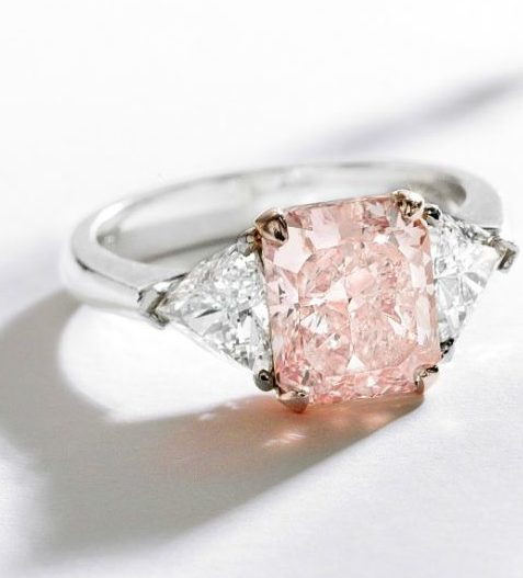 Pink diamond and diamond ring with a cut-cornered rectangular modified brilliant-cut fancy light pink diamond weighing 3.03 carats, which is flanked by two modified triangular-cut diamonds weighing approximately 1.00 carat. Via Diamonds in the Library