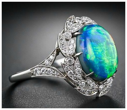Side view; a fire opal and diamond ring from Lang Antiques. Via Diamonds in the Library.