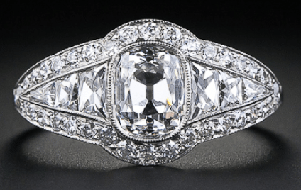 1.00 carat antique cushion cut diamond engagement ring. The central 1.00 carat cushion-cut is flanked on each side by a flash of custom-cut tapered French-cut diamonds.