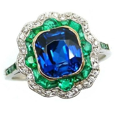 Art Deco sapphire, diamond, and emerald ring, circa 1915. A cushion-cut sapphire within a shaped cushion double border of emeralds and diamonds, and emerald line shoulders.